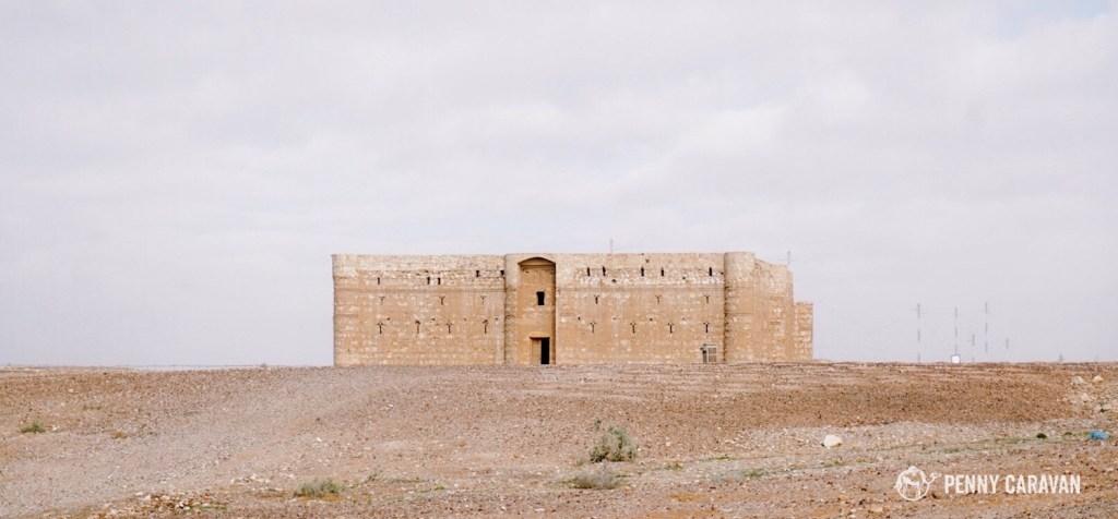 Qasr Kharana stands isolated on the flat desert landscape.