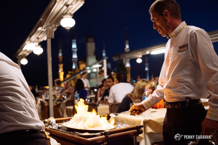 Rooftop of Seven Hills Restaurant, with a waiter serving a flaming salt-crusted fish.