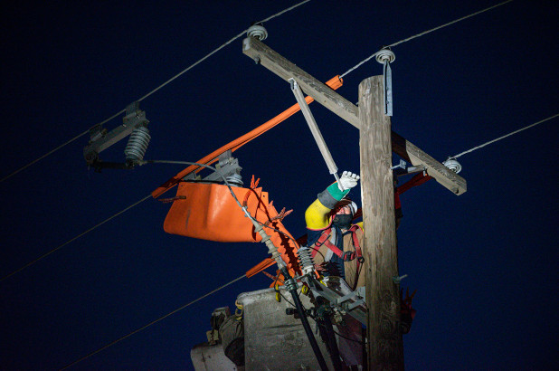 Brendan Waldon repairs a utility pole that was damaged by the winter storm that passed through Texas on Feb. 18, 2021, in Odessa, Texas.