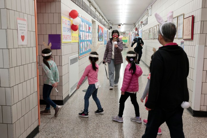 Principal Alice Hom welcomes students back to their classroom after they took part in a bunny hop in the schoolyard for K and Pre-K students at Yung Wing School P.S. 124.
