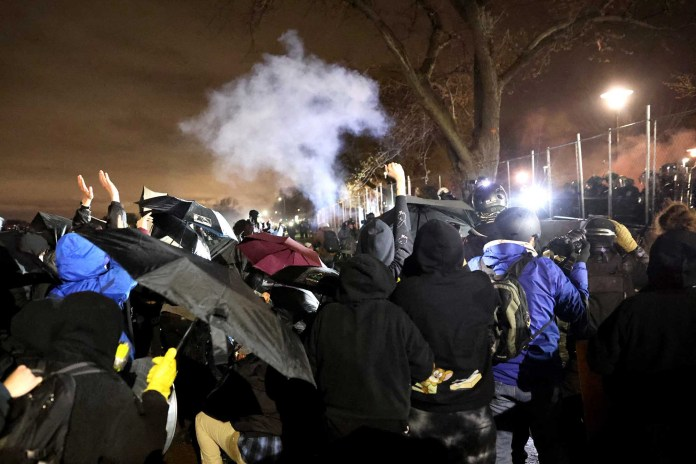 A cloud of smoke hangs over demonstrators during a protest at the Brooklyn Center police station on April 14, 2021 in Brooklyn Center, Minnesota