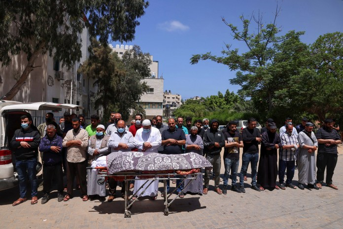 People offer funeral prayers next to the body of a Palestinian who was killed.