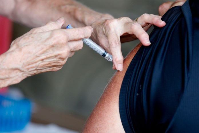 man receives a COVID-19 vaccine at a clinic in Springfield
