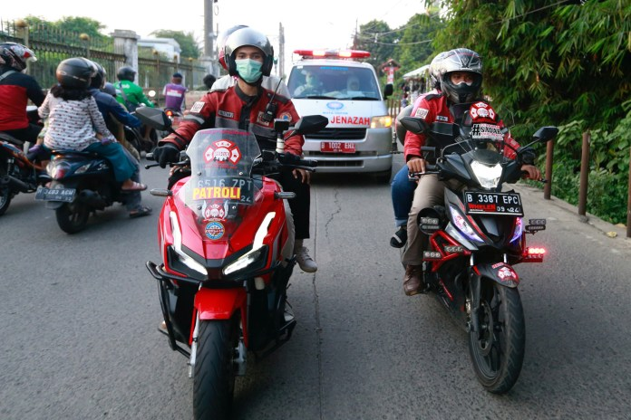 Volunteer bikers escort an ambulance to a cemetery as coronavirus disease (COVID-19) cases surge in Depok on the outskirts of Jakarta, Indonesia, July 2, 2021