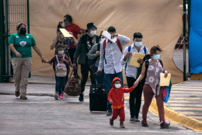 Asylum seekers walk to the U.S.-Mexico border as a group of at least 25 immigrants were allowed to travel from a migrant camp in Mexico
