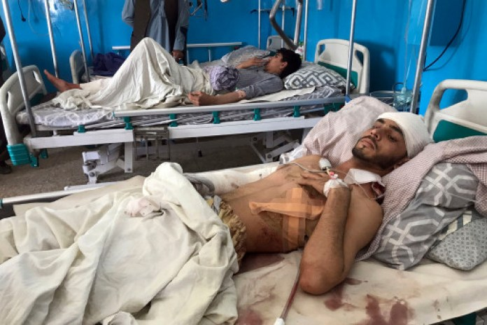 Afghans lie on beds at a hospital wounded after the deadly suicide bombing outside the airport in Kabul, Afghanistan on August 27, 2021.