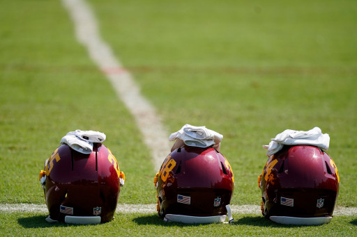 A line of helmets and gloves sits on the field during Washington Football Team practice.