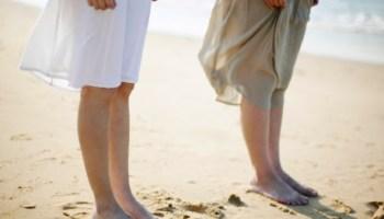 Two Women Standing Side by Side on Sandy Beach