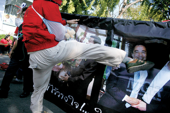 '총리를 향해, 돌려차기~!' 팔을 다쳤는지 보호대를 찬 채 '붉은 셔츠' 시위에 가담한 한 젊은이가 아피싯 웨차치와 총리가 웃고 있는 사진에 발길질을 하고 있다.(Photo by Lee Yu Kyung)