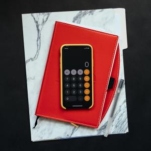 A phone showing a calculator app on top of file folders