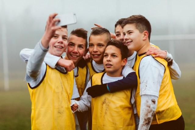 Illustrasjonsbilde som viser en gjeng fotballgutter som tar selfie