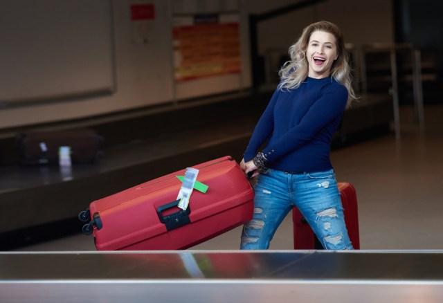Ung dame henter baggasjen fra et bagasjebånd