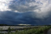 Massive dark storm clouds approaching above the river