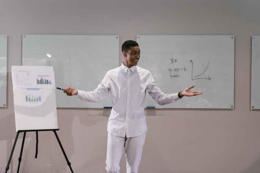 a man in white long sleeve presenting report in the meeting room