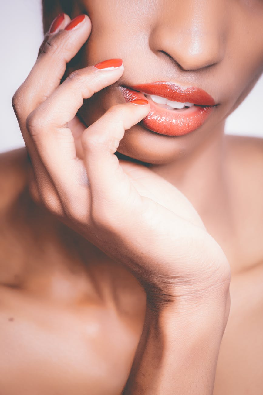 woman with orange lipstick and manicure taking selfie