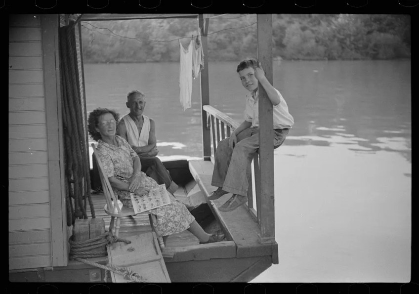 Family on front porch of houseboat on river in Charleston, West Virginia-1938