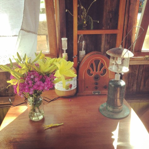 The work/galley table with flowers from Shireen, old-timey radio from James, and Kai's apple hooch a'brewin'.
