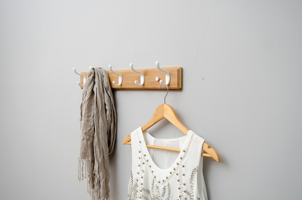 adolescentes organizados: un perchero de pared con ropa colgada
