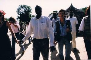 Riek Machar camina de la mano de su segunda esposa, la británica Enma McKuen, en su aldea natal, Leer. Entre ambos aparece la directora de USAID tras mantener una reunión con el líder guerrillero. (Foto: LUIS DAVILLA)