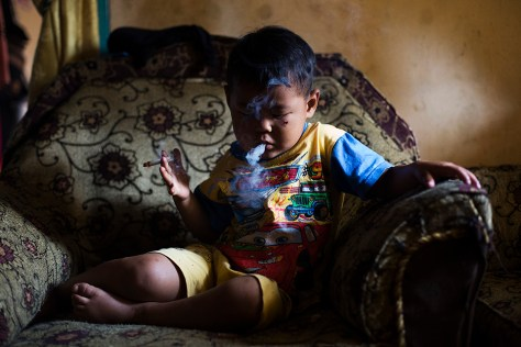 Five-year-old Ardian Azka Mubarok smokes at his home in near Garut, Indonesia on March 27, 2015. (Photo By: Michelle Siu)