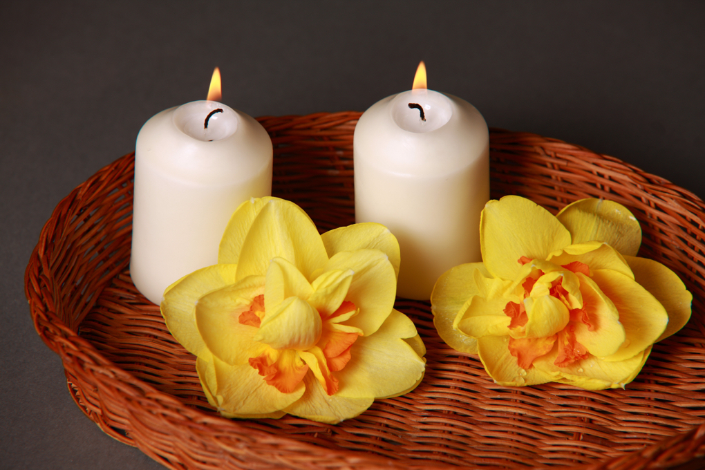 Photo of burning candles beside flowers in a basket as a way to help get your mind ready for the day as part of getting started on a healthier lifestyle