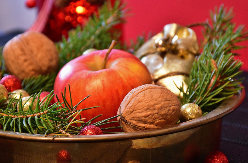 Photo of bowl of nuts and an apple for staying healthy during the holidays