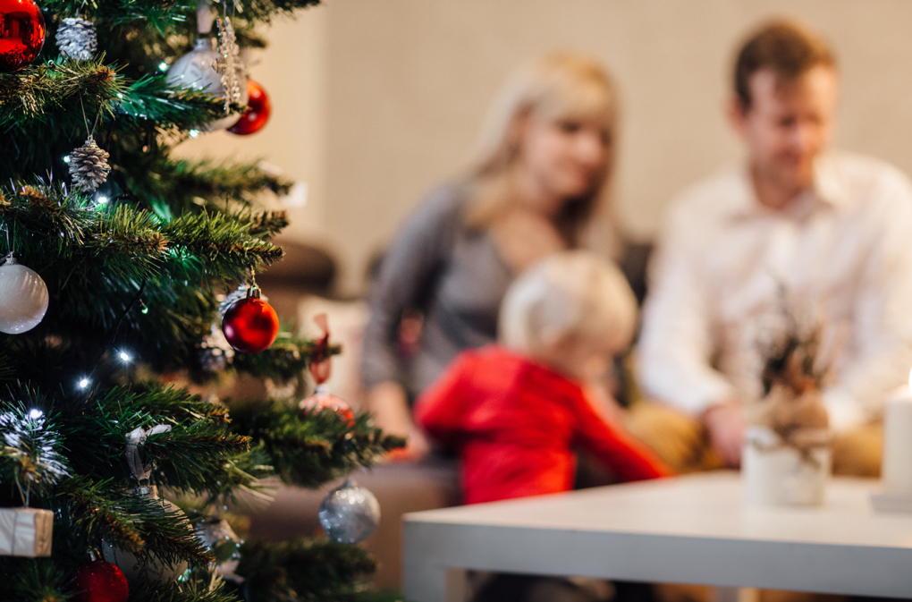 Photo of family sitting near a Christmas tree as a common tradition