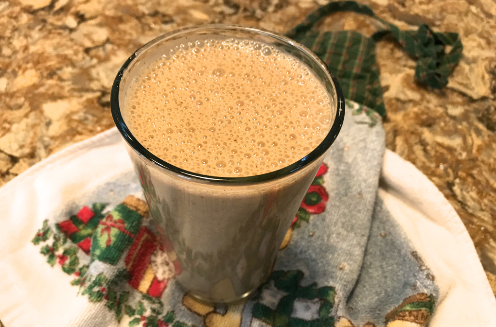 Photo of Healthy Vegan Gingerbread Cookie Smoothie in clear glass on holiday dish towel