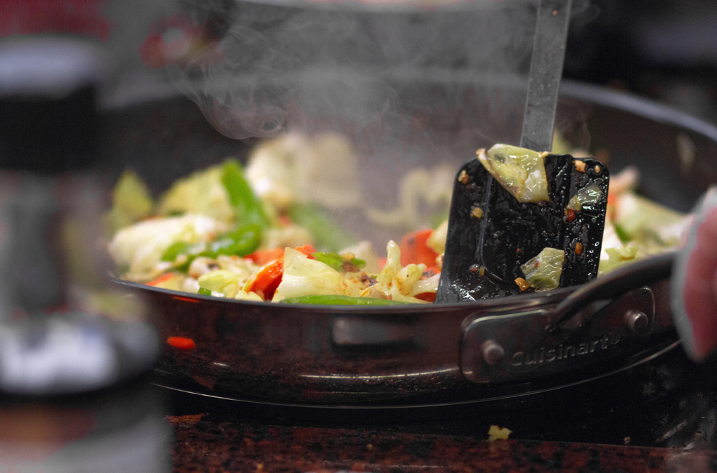 Photo of steaming vegetables in a skillet being cooked and stirred as an example of healthy eating.