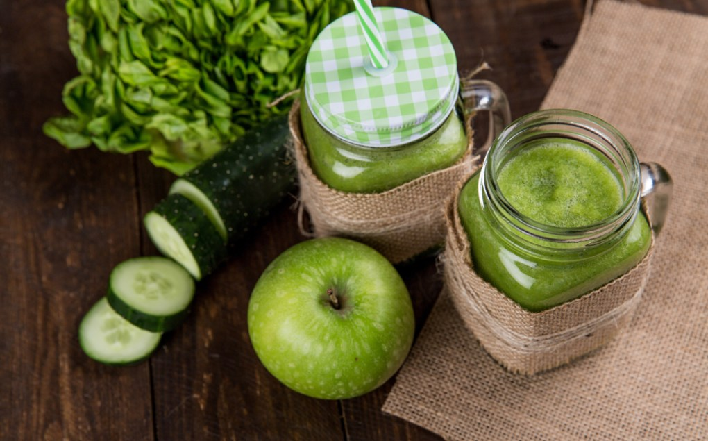 Photo of green smoothies sitting by a cucumber and a green apple as an example of healthy eating.