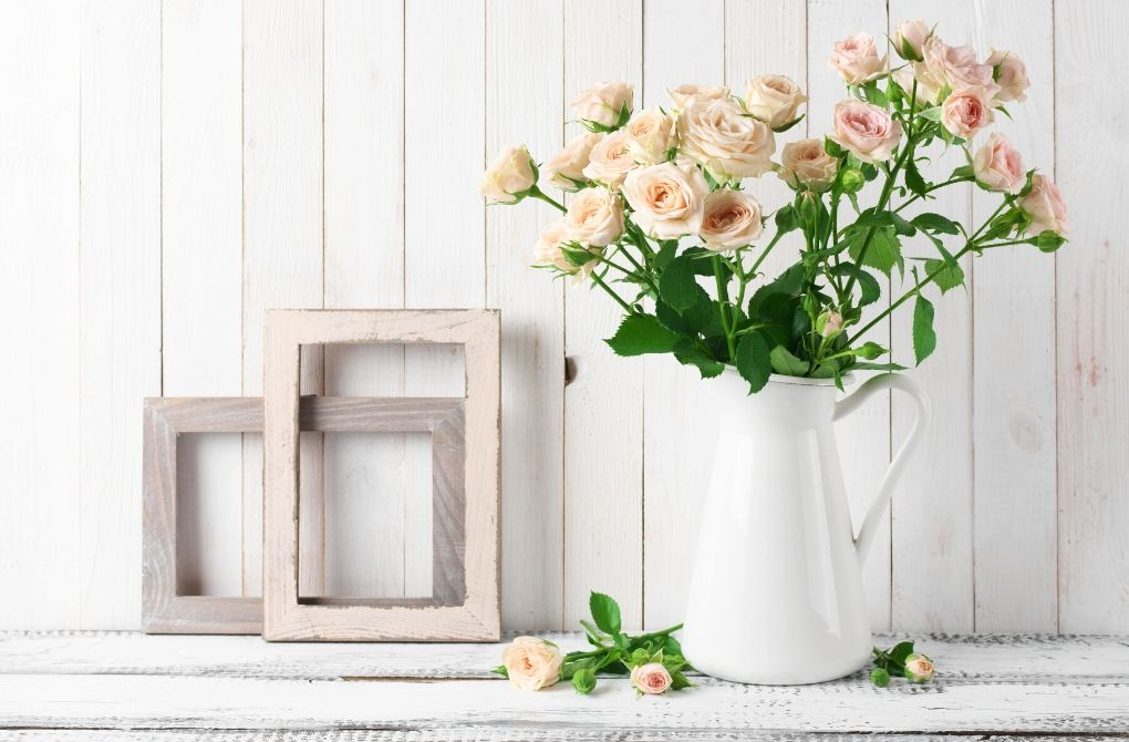 Photo of pot of pink flower and empty wooden picture frames as an example of seasonal decorating