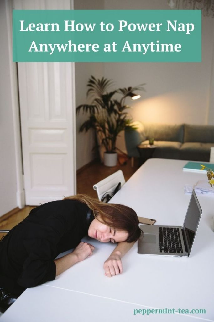 Photo of woman sleeping with her head down on a table in front of her computer as an example of how to power nap