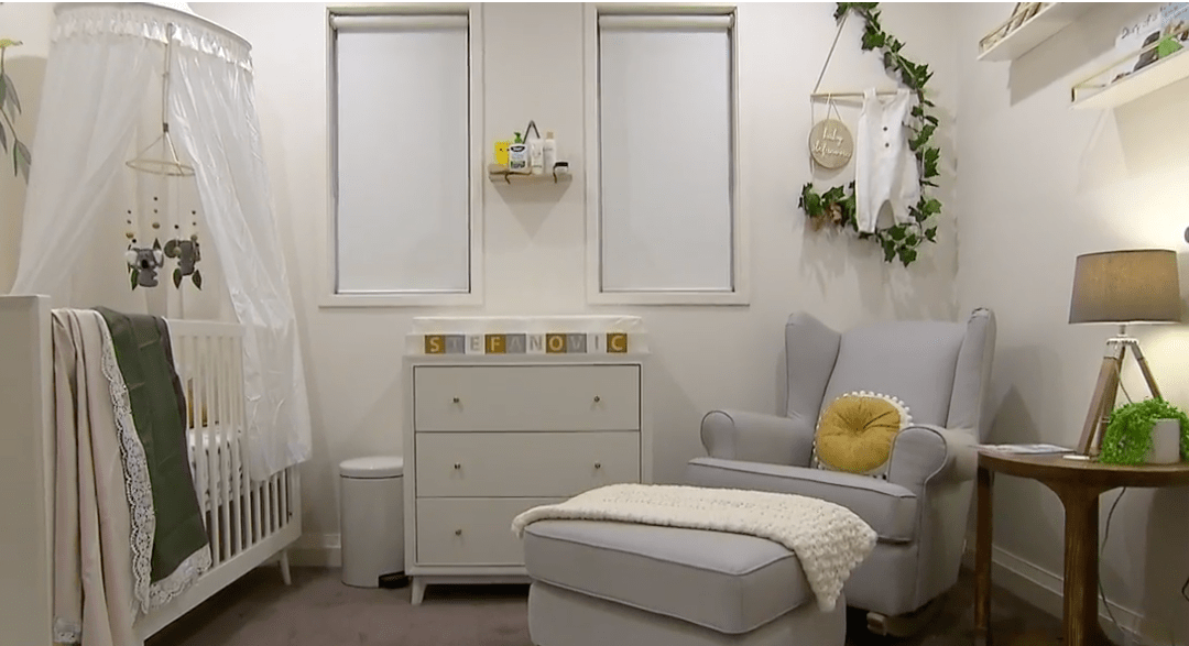 Full Room Shot of Sylvia Jeffreys Modern Australiana Nursery - Cot with canopy and mobile, chest of drawers and feeding chair and then bookshelves on wall. Colour theme white, mustard, light grey and greens