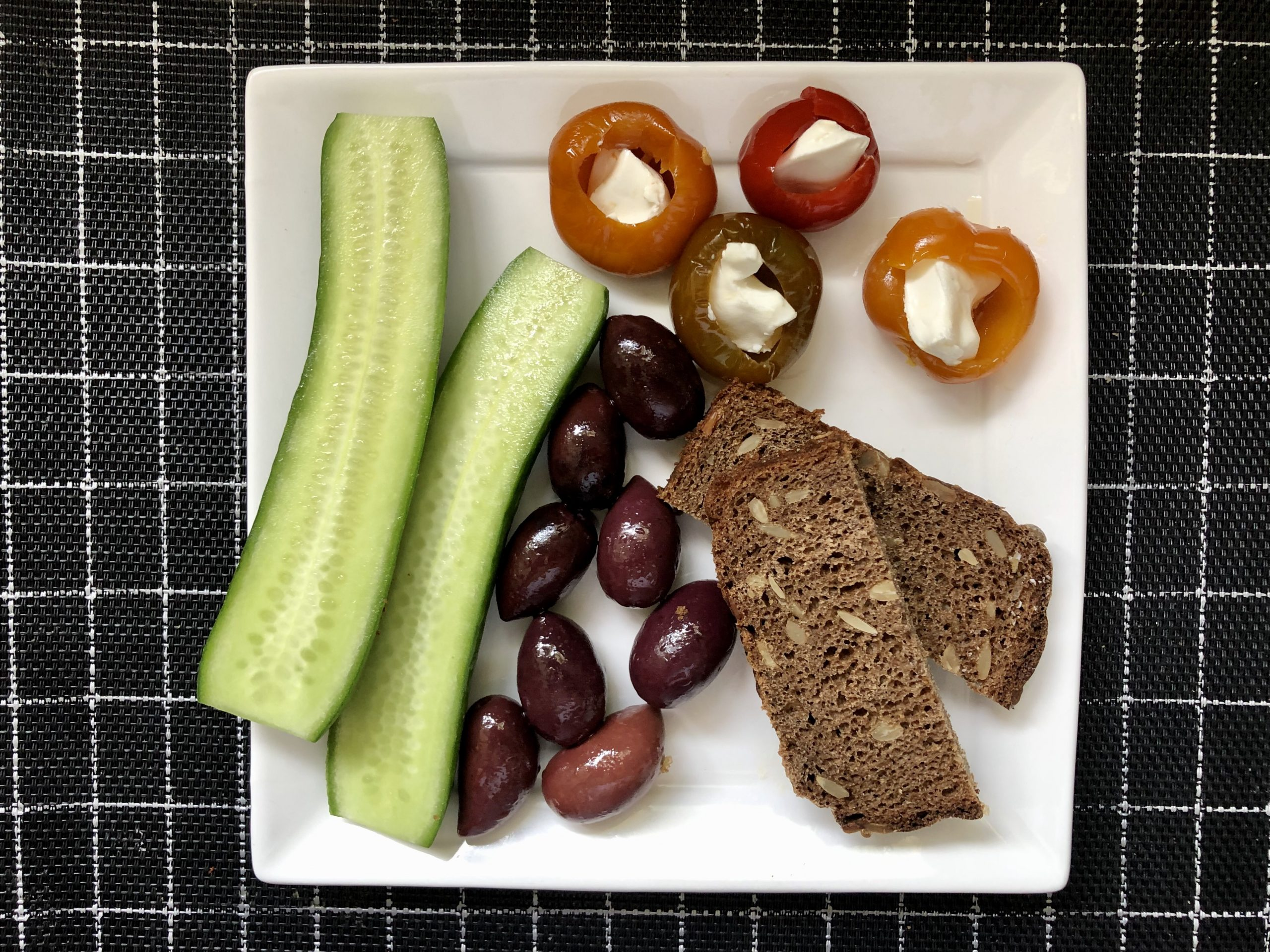 Mediterranean breakfast: marinated peppers stuffed with goat cheese, kalamata olives, cucumber and rye bread