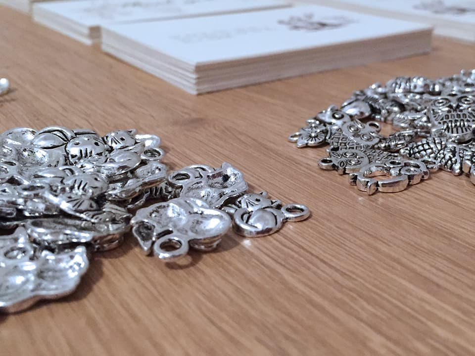 Closeup photo of the small metal owl charms that we included on our handmade wedding invitations