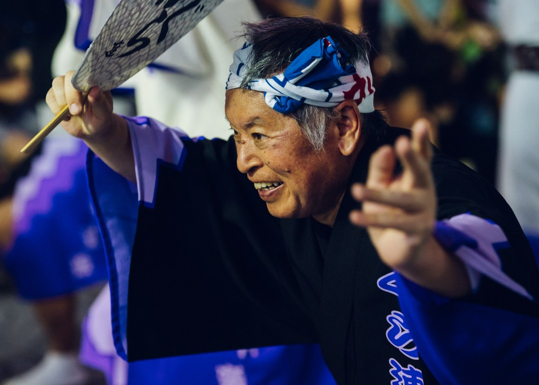 An Japanese man smiles as he participates in Awa Odori.