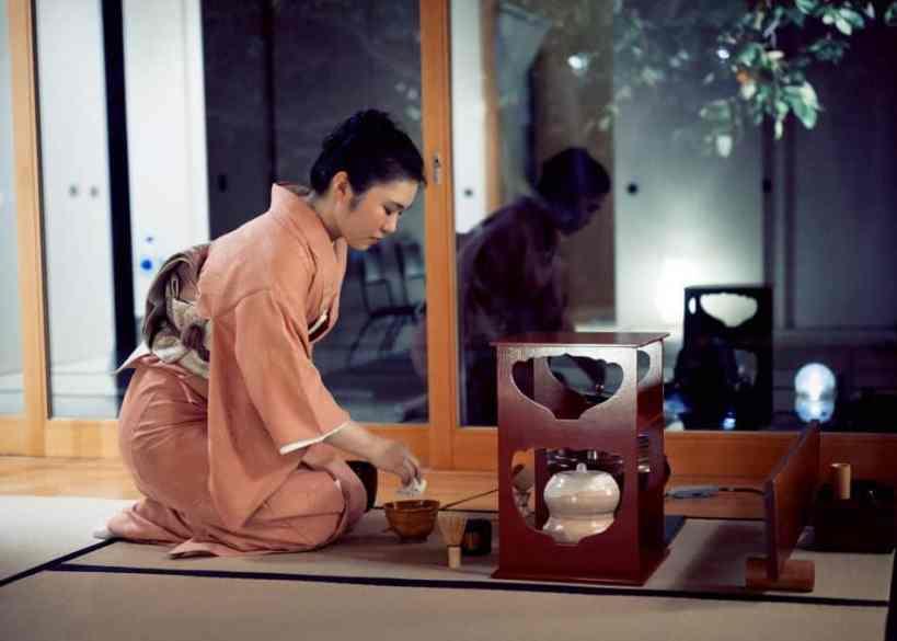 Woman prepares to serve tea during Japanese tea ceremony