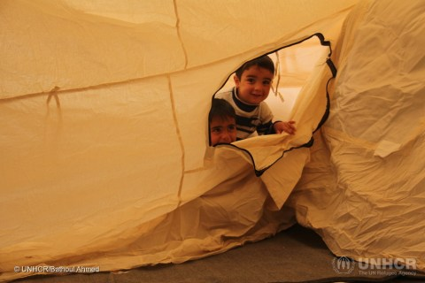 Two young Iraqi boys, their family displaced by the fighting in Mosul, peek out through the zipper of their tent at Hasansham camp, as UNHCR delivers cold weather supplies, including warm blankets and stoves. ; After two years trapped inside Iraq's second largest city, thousands of Iraqis are relieved to be free of tyrannical militant rule. But with the onset of winter and temperatures beginning to fall, UNHCR must now deliver life-saving cold weather equipment to millions of displaced Iraqis and Syrians. In preparation for the military operation in Mosul which began in October 2016, UNHCR pre-planned the construction of 11 new camps, designed to accommodate 120,000 people. Emergency plans are also in place to provide tents and supplies to those who cannot access the camps. Around 3.3 million Iraqis, ten per cent of the population, have fled their homes since March 2014. © UNHCR/Photographer