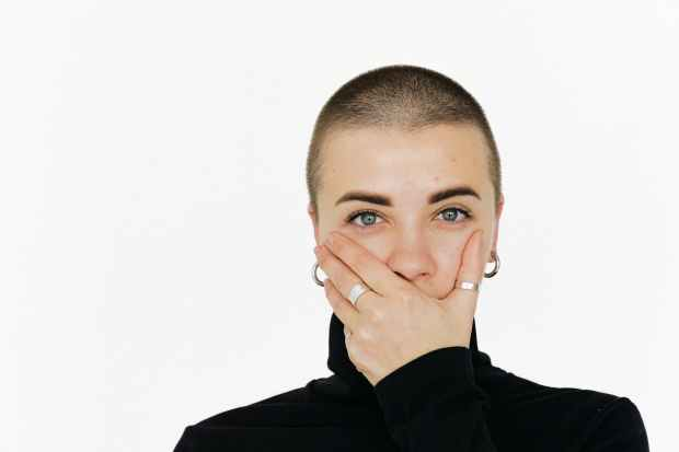 woman in black top covering her mouth