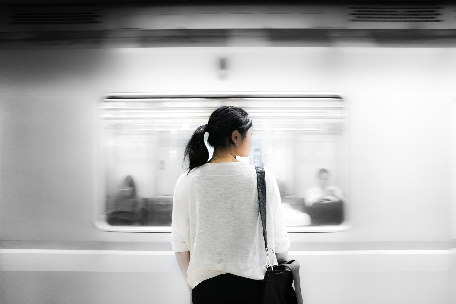 Asian American woman standing at train station.