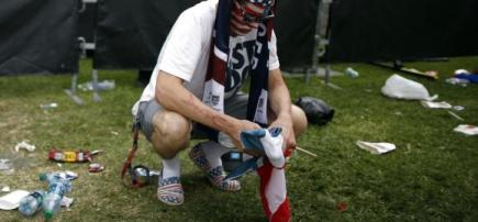 USA fan Steve Essex crouches with a U.S. flag after the U.S. was defeated by Belgium, in Redondo Beach