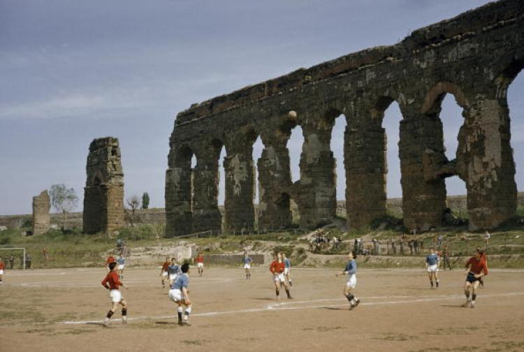 Boys play soccer beside arches of ancient aqueduct