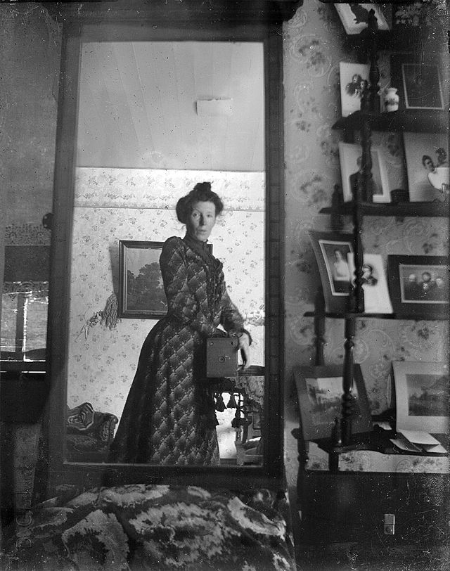Unidentified_woman_taking_her_own_photograph_using_a_mirror_and_a_box_camera,_roughly_1900