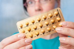 woman holds birth control pills
