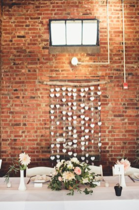 DIY headtable decor at Seattle wedding with paper hearts against brick wall   Golden Gardens Bathouse Wedding   Perfectly Posh Events, Seattle Wedding Planner   Andria Linquist Photography   Holly + Dustin Wedding // © Andria Lindquist 2014