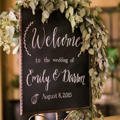 Sodo Park with Herban Feast Wedding in Seattle | Real Wedding use of 2017 Pantone Color of the Year | Welcome sign with lush greenery swag with romantic pink, and maroon blooms | Perfectly Posh Events, Seattle Wedding Planning | Kimberly Kay Photography | Floral Design by Floressence