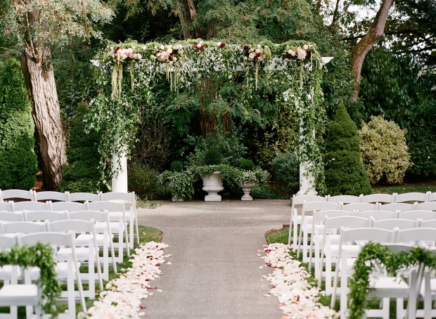 Laurel Creek Manor Wedding in Sumner | Stunning, lush greenery swag for outdoor ceremony altar | Design + Coordinated by Perfectly Posh Events | Katie Parra Photography | Floral Design by Flora Nova