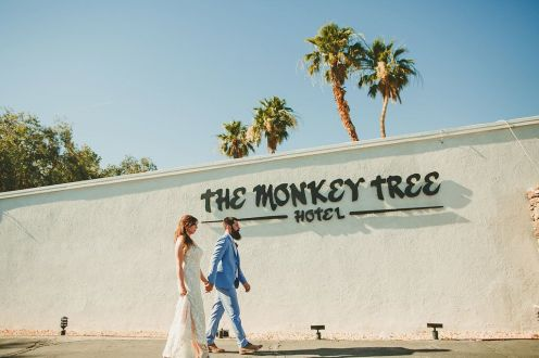 The Monkey Tree Hotel, Palm Springs wedding venue | bride and groom in front of hotel sign | Perfectly Posh Events, Seattle and Portland Wedding Planner