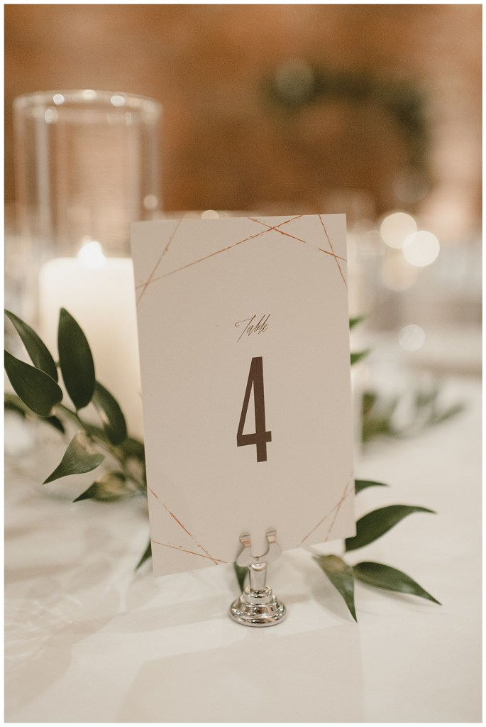 Custom wedding table number accessorized with green leaves, Axis Pioneer Square wedding, Seattle wedding, planning and design by Perfectly Posh Events, Seattle Wedding Planner, Photo by Carina Skrobrecki