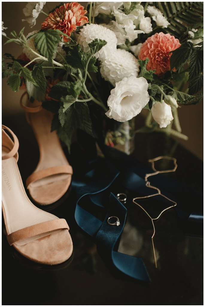 Strappy nude heels sit with a navy tie and two wedding bands with an ivory and coral colored floral bouquet, Axis Pioneer Square wedding, Seattle wedding, planning and design by Perfectly Posh Events, Seattle Wedding Planner, Photo by Carina Skrobrecki